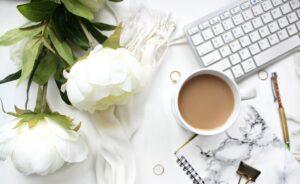 デスクに白いお花とコーヒーの画像